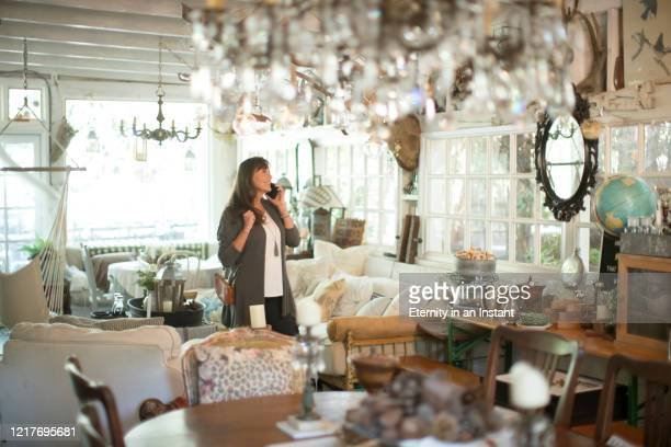 mature woman shopping in an antique store - gift shop stock pictures, royalty-free photos & images