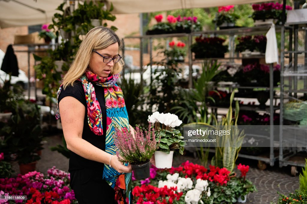 Mature woman shopping in street flower market outdoors. : Stock Photo