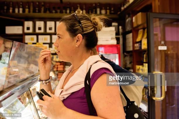 """reife frau einkaufen in straßenmarkt im freien. - """"martine doucet"""" or martinedoucet stock-fotos und bilder"""