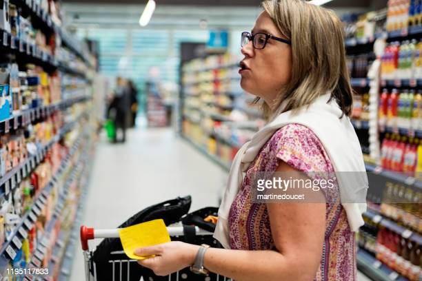 """mature woman shopping in supermarket. - """"martine doucet"""" or martinedoucet stock pictures, royalty-free photos & images"""