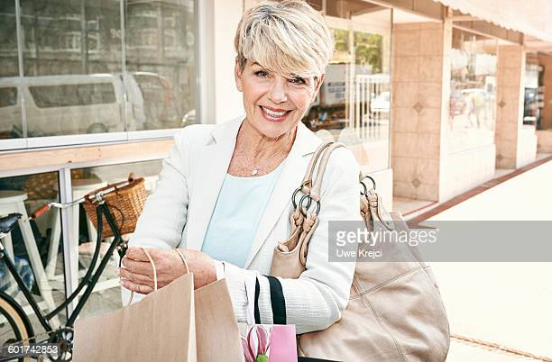 Mature woman shopping on village street