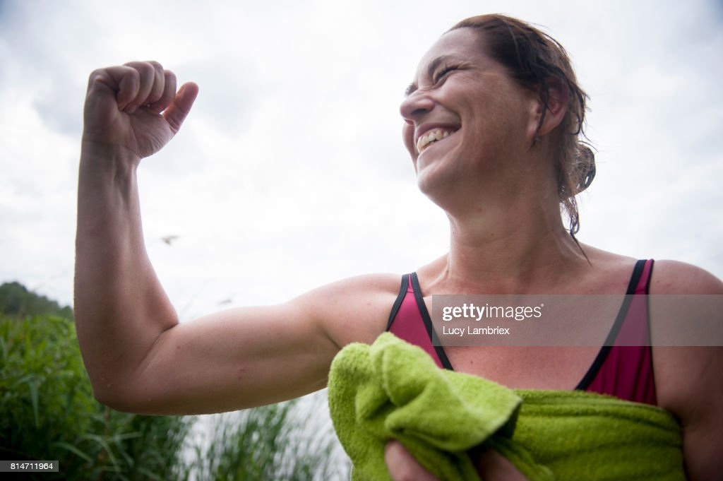 Mature woman showing her muscles after swimming in open water : Stock Photo