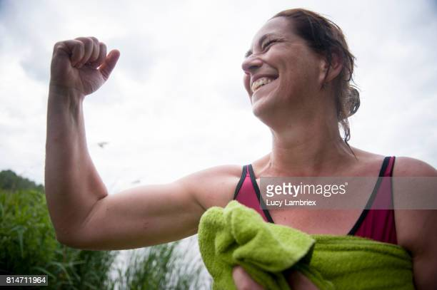 Mature woman showing her muscles after swimming in open water