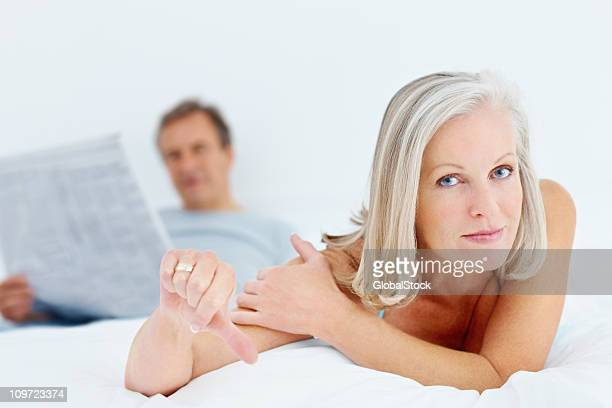 Mature woman showing thumbs down sign in bed