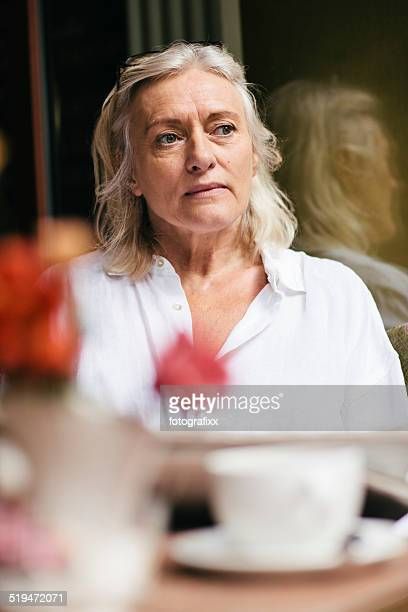 mature woman sits in a cafe and reads newspaper
