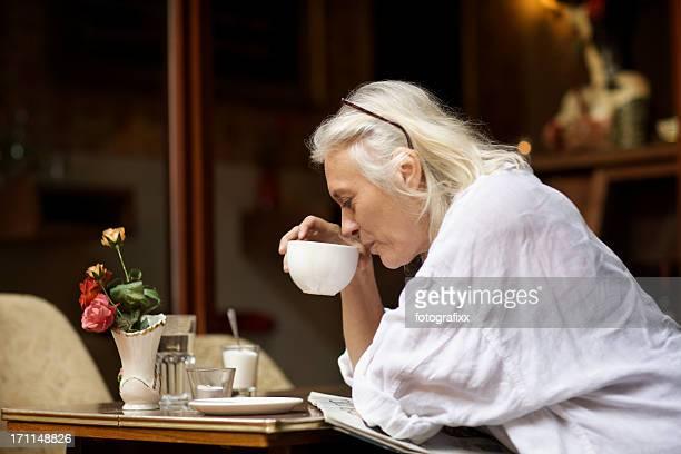 Reife Frau sitzt in einem Café und liest die Zeitung