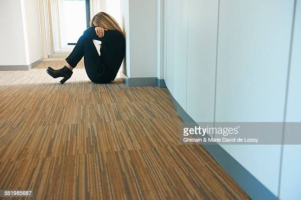 Mature woman sitting against wall in corridor