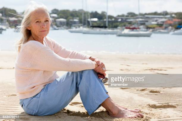 Mature woman sitting and dreaming on the beach, copy space