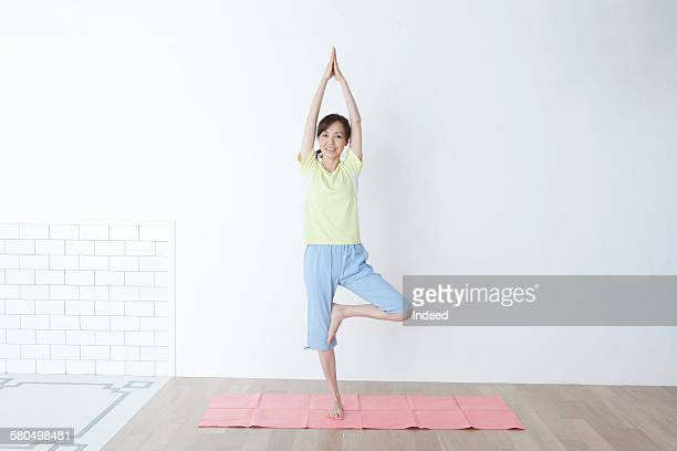 Mature woman sitting  and smiling on yoga mat