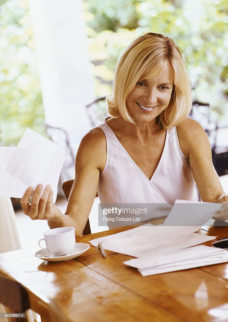 Mature Woman Sitting at a Table Organising Her Bills : Stock Photo