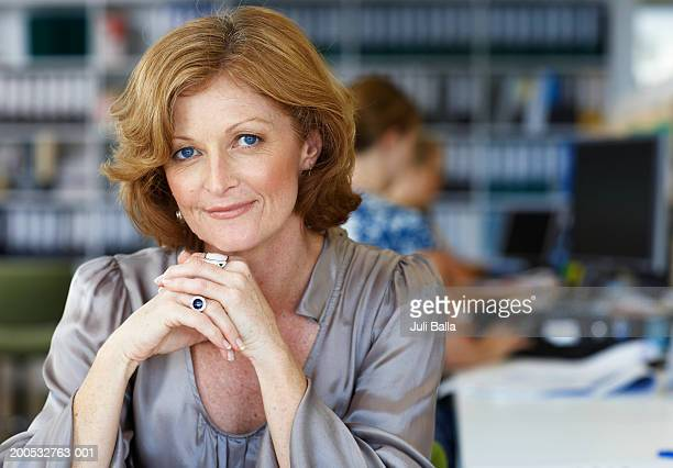 Mature woman sitting at desk in office, smiling, portrait