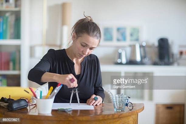 mature woman sitting at desk, using pair of compasses - sigrid gombert foto e immagini stock