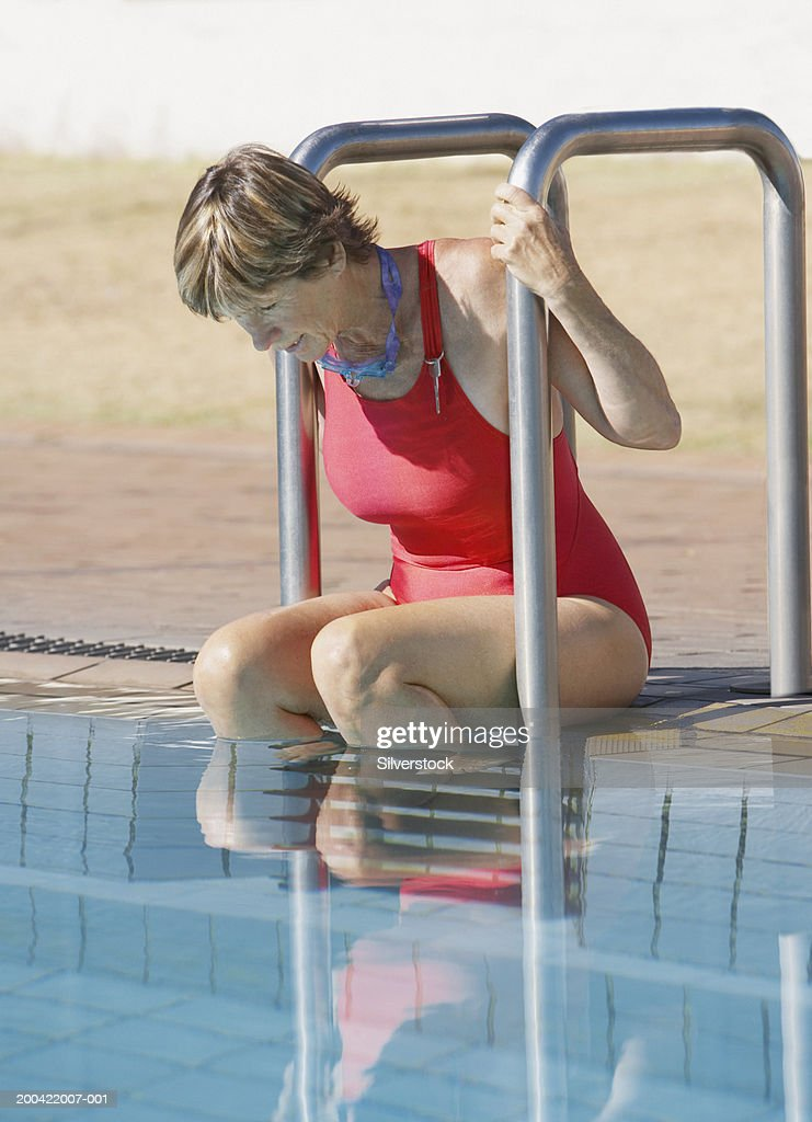 Mature Woman Sitting At Edge Of Swimming Pool Wearing Swimsuit High-Res Stock Photo -2007