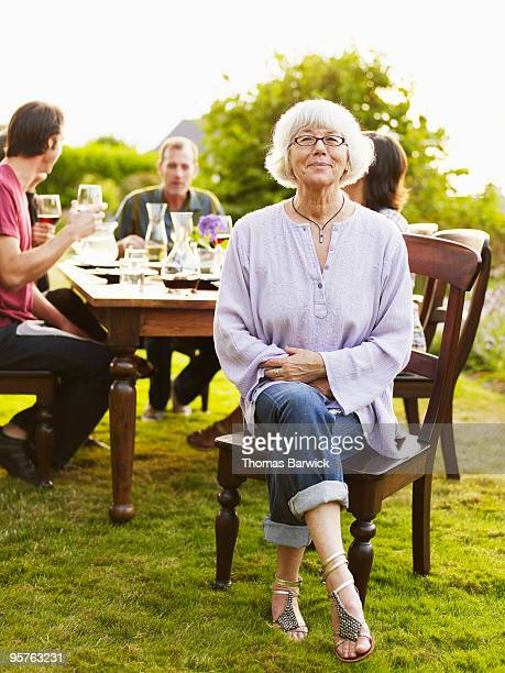 Mature woman sitting at head of outdoor table