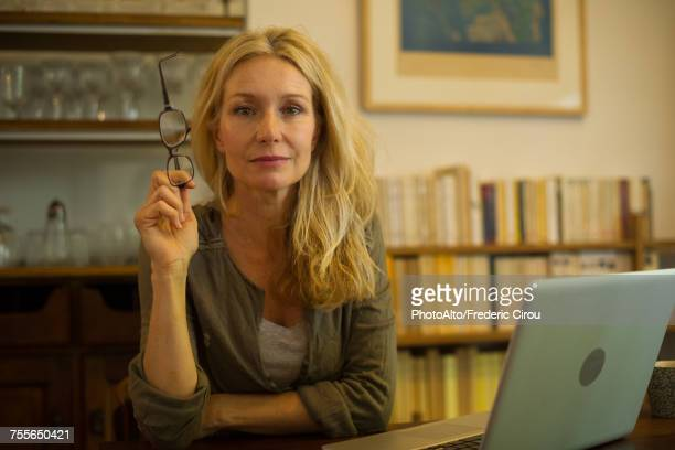 mature woman sitting at home with laptop computer, portrait - authors photos et images de collection