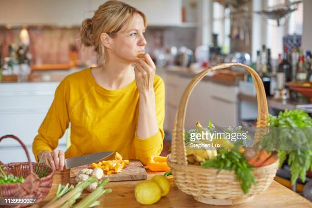 mature woman sitting at kitchen table, chopping vegetables - one mature woman only stock pictures, royalty-free photos & images
