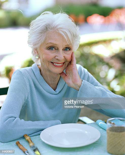 Mature woman sitting at outside table, portrait