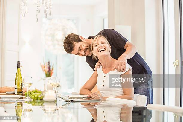 Mature woman sitting at table while mature man looks over her shoulder, laughing