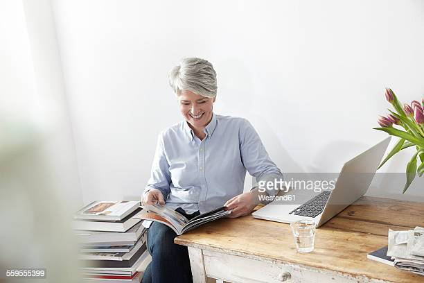 Mature woman sitting at table with magazine and laptop