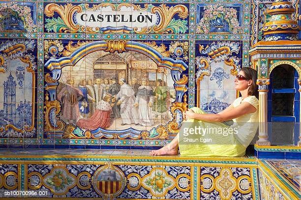 mature woman sitting by tile mosaic saying 'castellon' - castellon province stock pictures, royalty-free photos & images