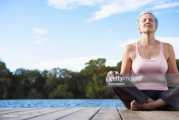 mature woman sitting crossed legged by lake, eyes closed - low angle view photos et images de collection