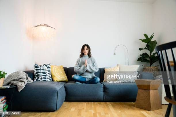 mature woman sitting cross-legged on couch with eyes closed, meditating at home - spiritualiteit stockfoto's en -beelden