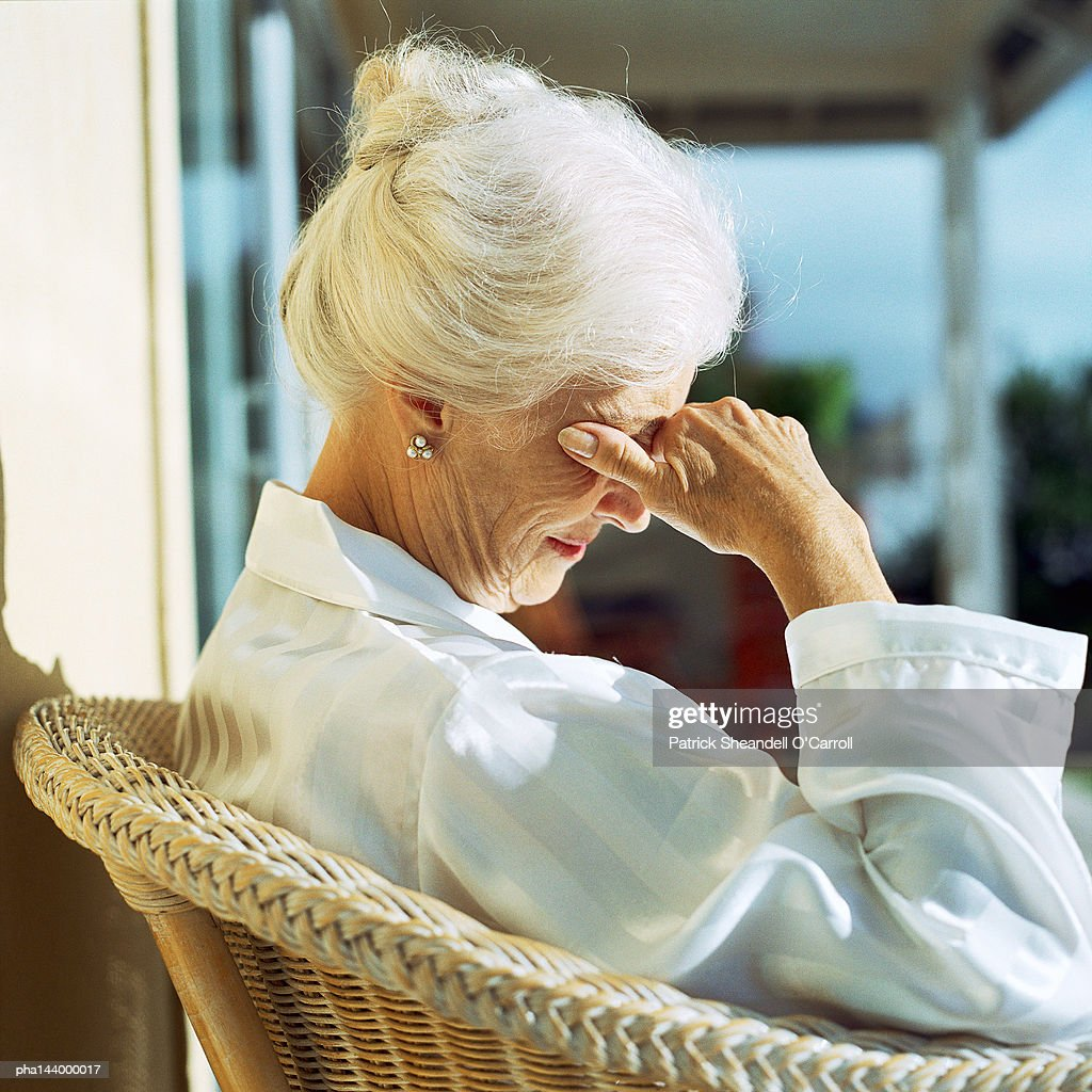 Mature woman sitting, hand on face, side view : Stockfoto