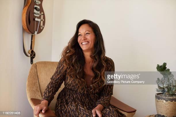 femme mûr s'asseyant dans une présidence à la maison et riant - une seule femme d'âge mûr photos et images de collection