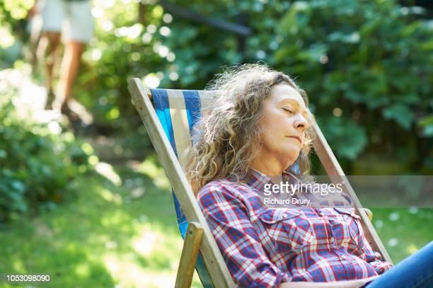 Mature woman sitting in a deckchair relaxing in the garden