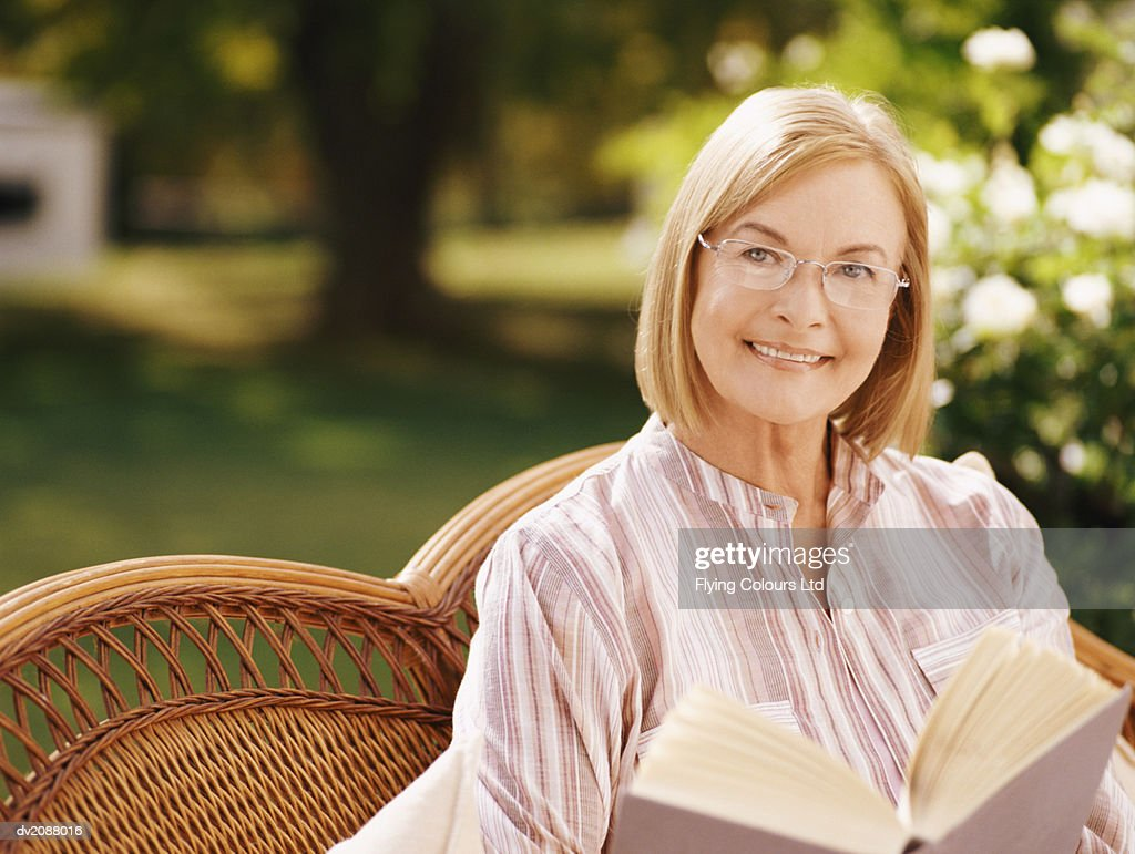 Mature Woman Sitting in a Garden Reading a Book : Stock Photo