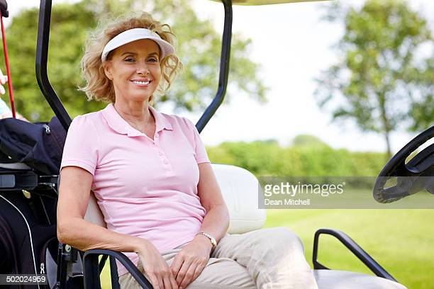 Mature woman sitting in a golf cart smiling