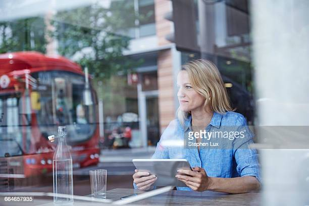 Mature woman sitting in cafe, using digital tablet, bus reflected in window