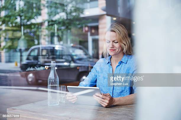 Mature woman sitting in cafe, using digital tablet, taxi reflected in window