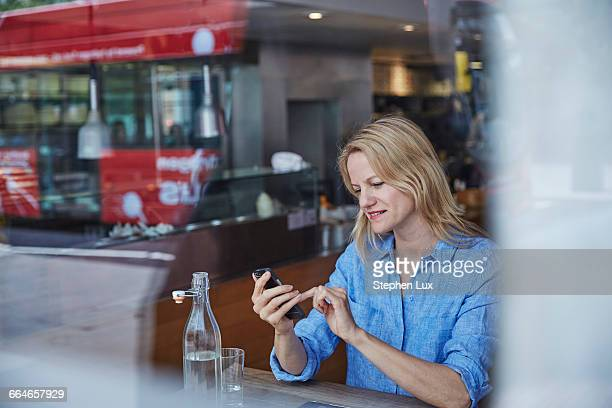 Mature woman sitting in cafe, using smartphone, bus reflected in window