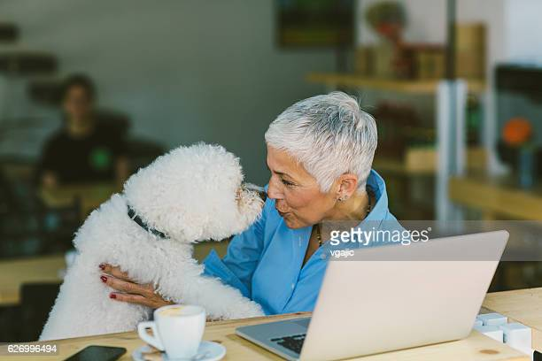 Mature Woman Sitting In Cafe With Her Dog
