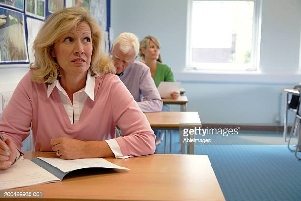 Mature woman sitting in classroom, eyebrows raised