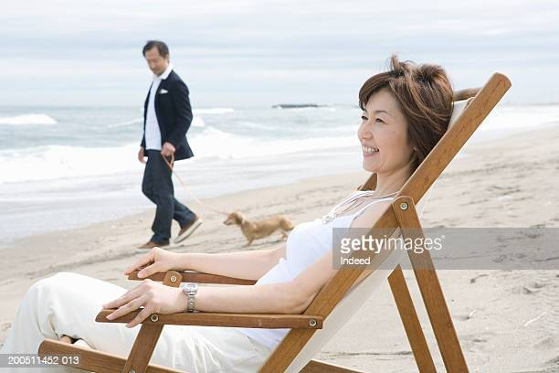 Mature woman sitting in deckchair on beach, man walking dog