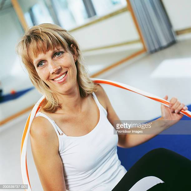Mature woman sitting in exercise class holding hoop, smiling