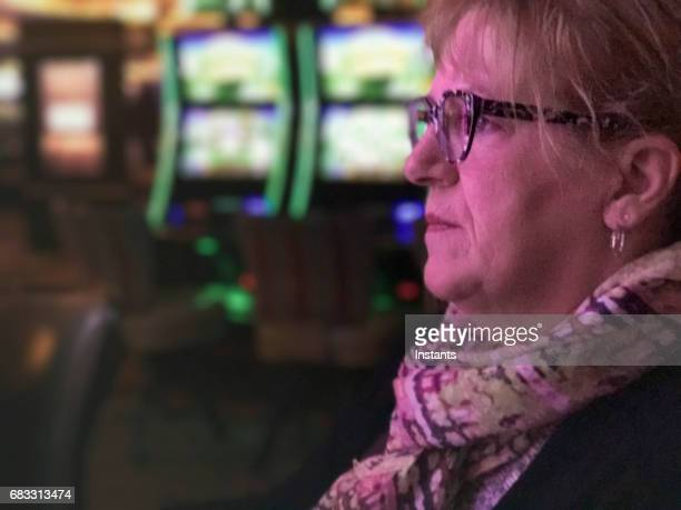 a mature woman, sitting in front of a slot machine, is seriously checking the screen while gambling in a las vegas casino. - gambling addiction stock pictures, royalty-free photos & images