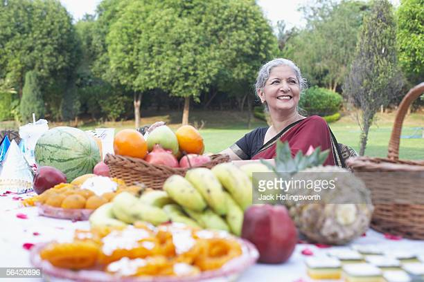 Mature woman sitting in front of a table of fruit and sweets