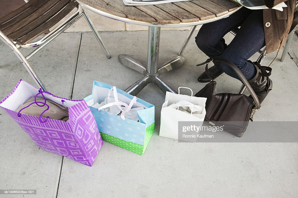 Mature woman sitting in outdoor cafT with shopping bags, low section : Foto stock