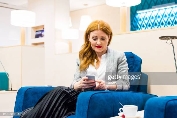 mature woman sitting in the aiport vip lounge in the evening - izusek imagens e fotografias de stock