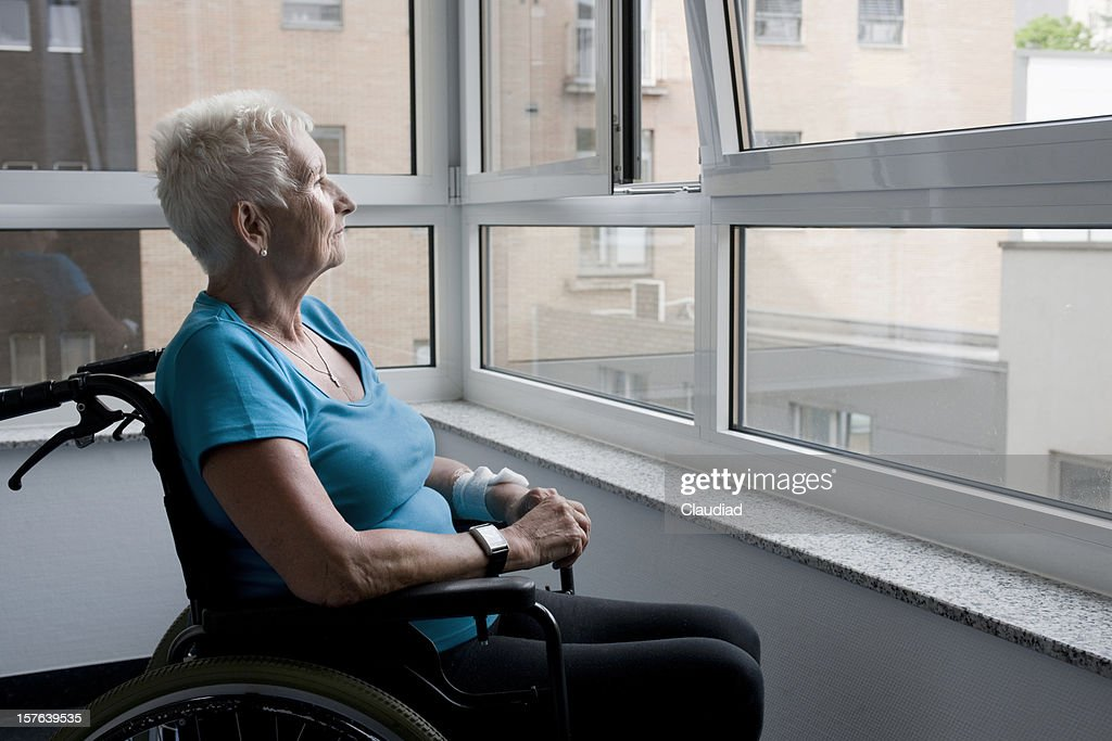 Mature woman sitting in wheelchair : Stock Photo