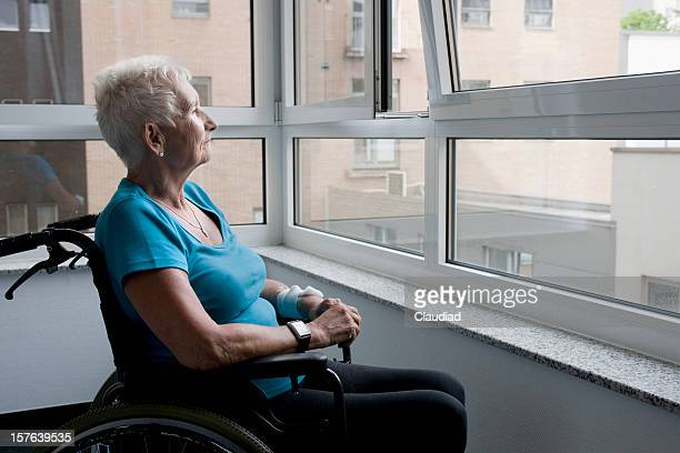 mature woman sitting in wheelchair - osteoporosis stock photos and pictures