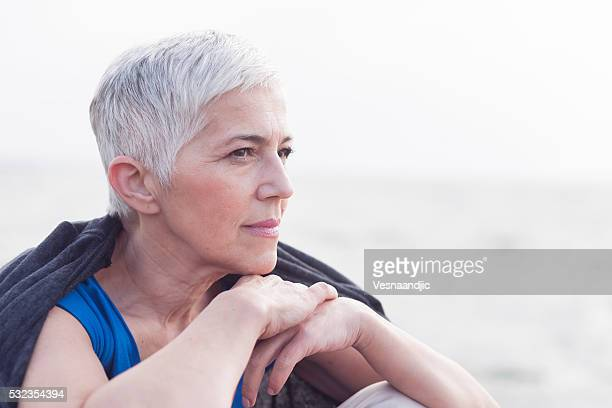 mature woman sitting near the sea - white hair stock photos and pictures