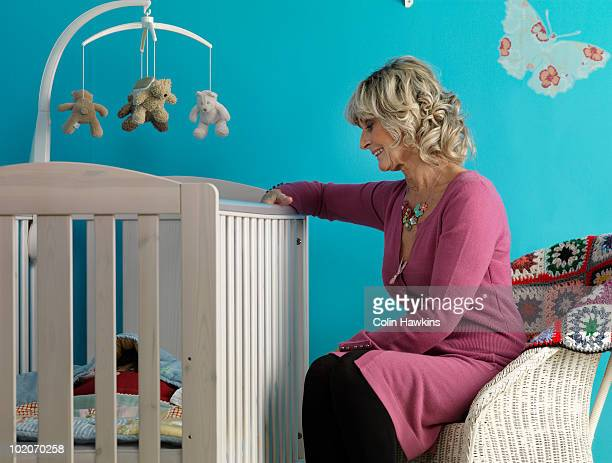 Mature woman sitting next to cot