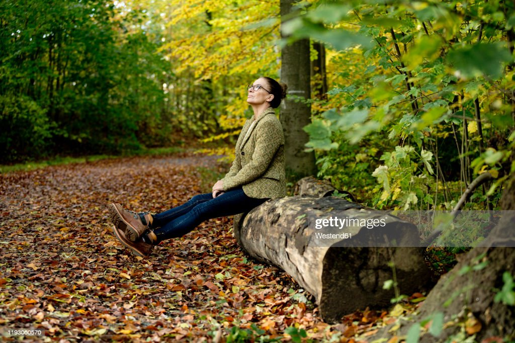 Mature woman sitting on a tree trunk in a autumn forest : Stockfoto