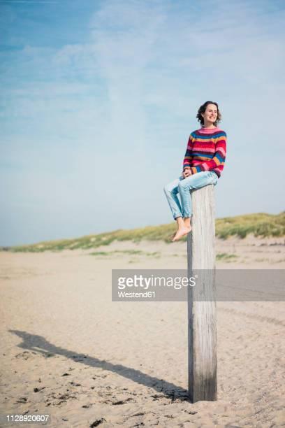 mature woman sitting on a wood pole on the beach - paal stockfoto's en -beelden