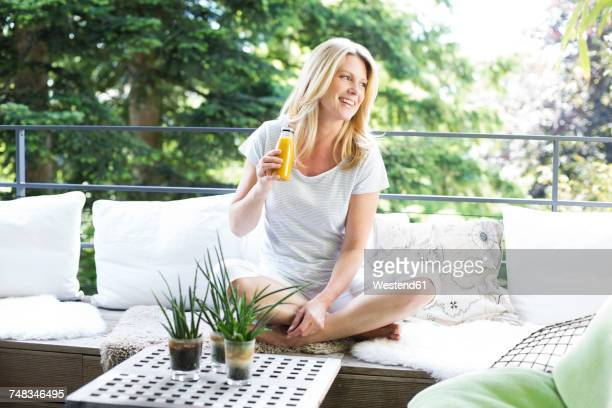 Mature woman sitting on balcony, drinking healthy smootis