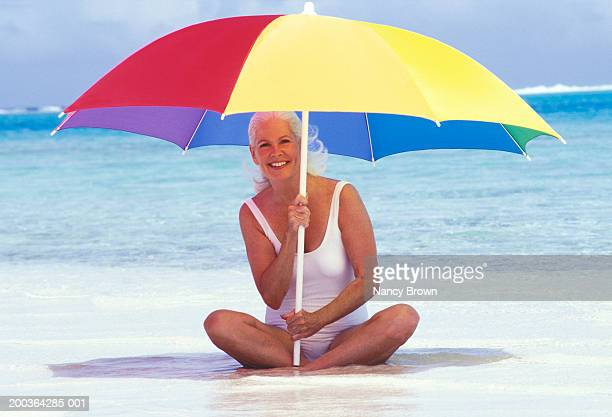 Mature woman sitting on beach, holding umbrella, portrait
